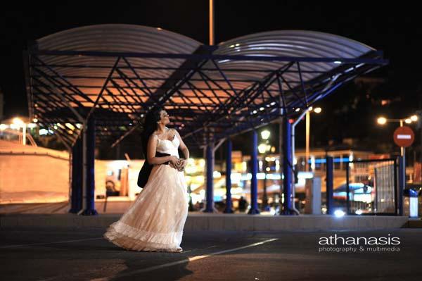 η νύφη στην αγκαλιά του γαμπρού με φόντο την αποβάθρα του λιμανιυ