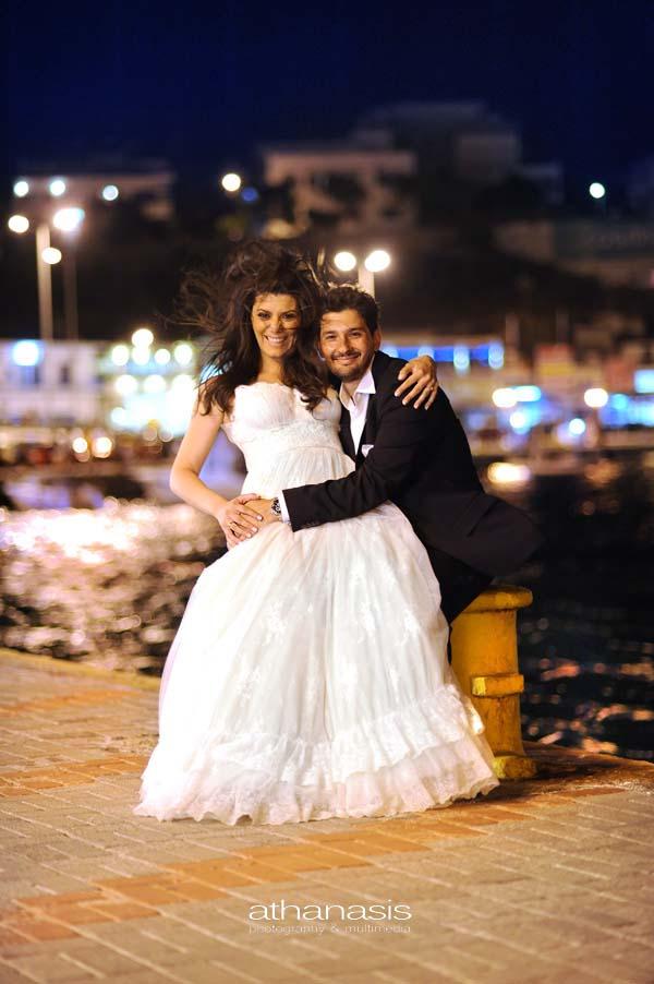 η νύφη στην αγκαλιά του γαμπρού στον κάβο του λιμανιού, δυνατός αέρας και χαμόγελα