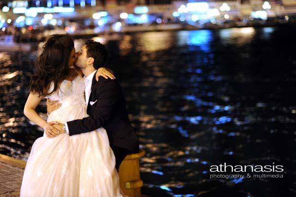 η νύφη στην αγκαλιά του γαμπρού, στον κάβο του λιμανιού την νύχτα
