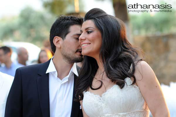 ο γαμπρός ψιθυριζεἰ στην χαμογελαστἠ νύφη