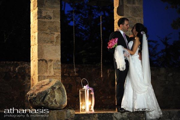 οι νεόνυμφοι αγκαλιά μπροστά στο καμπαναριό , έγχρωμη φωτογραφία γάμου