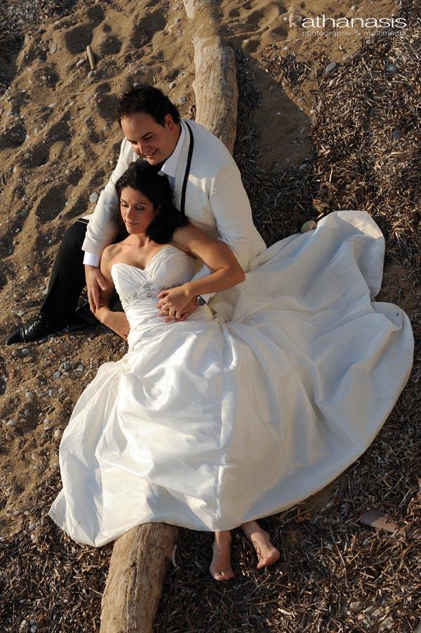 γαμπρός αγκαλιάζει την νύφη καθισμένος στην αμμουδιά