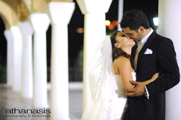 ο γαμπρός ακουμπισμένος σε μια κολόνα δέχεται τα φιλιά της νύφης