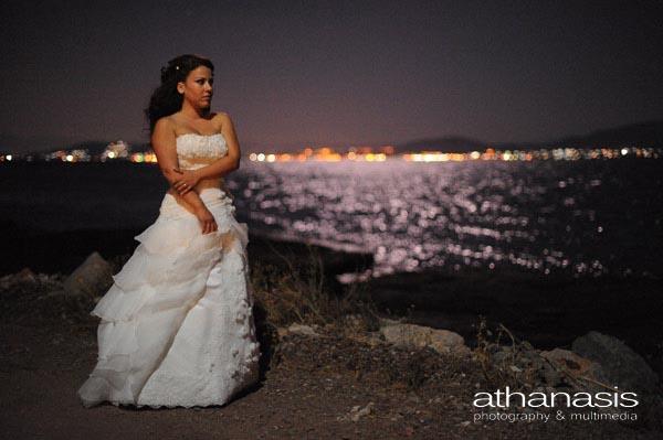 νυχτερινή φωτογραφία της νύφης στην θάλασσα που λαμπυρίζει