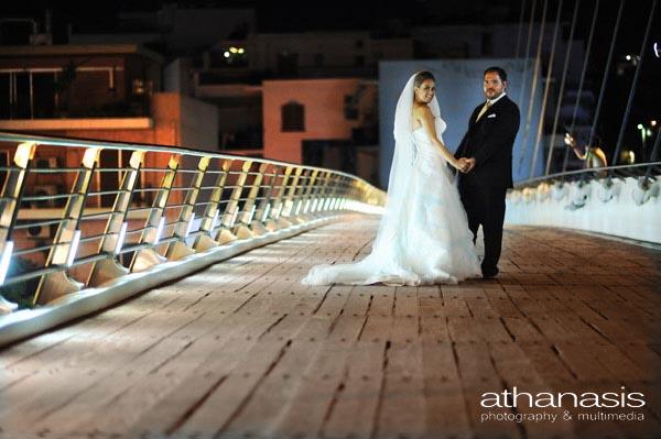 Νυχτερινή φωτογραφία γάμου, το ζευγάρι ποζάρει ολόσωμο πάνω στην γέφυρα