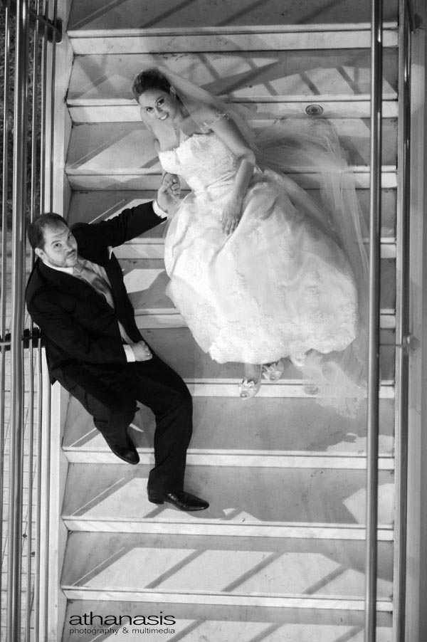 ΟΙ νεόνυμφοι φωτογραφημένη από ψηλά στις σκάλες . Νυχτερινή φωτογραφία γάμου.