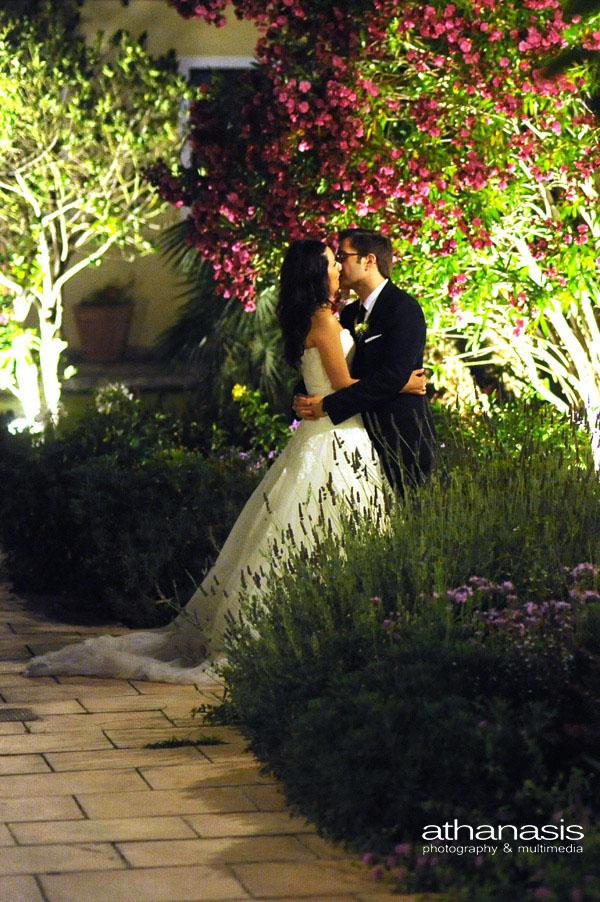 Νυχτερινή φωτογραφία γάμου , οι νεόνυμφοι σε μια γωνία του κήπου της δεξιωσης