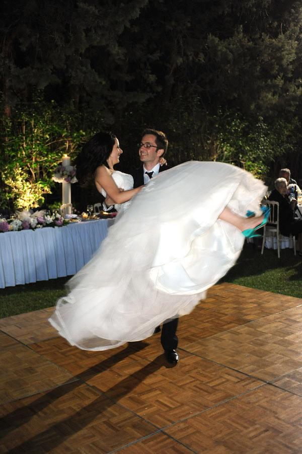 Ο γαμπρός κρατάει στην αγκαλιά του την νύφη και την περιστρέφει στον αέρα , στιγμή του χορού τους .